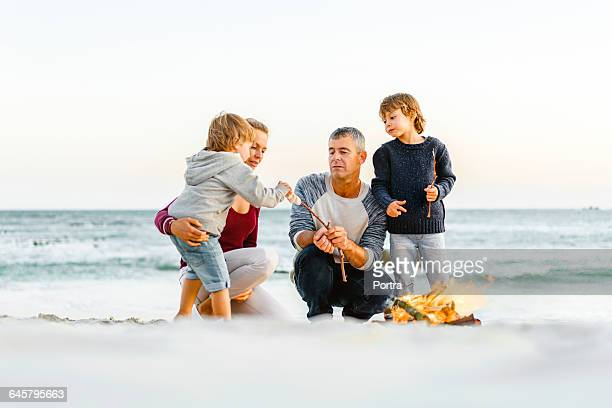 Parents are feeding son by campfire at beach