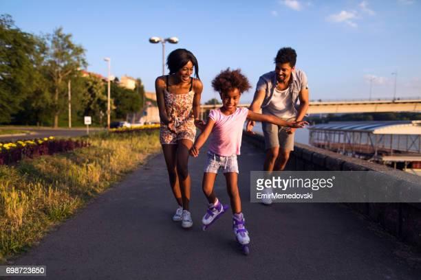 Eltern unterstützen ihre Tochter beim Rollschuhlaufen bei Sonnenuntergang.