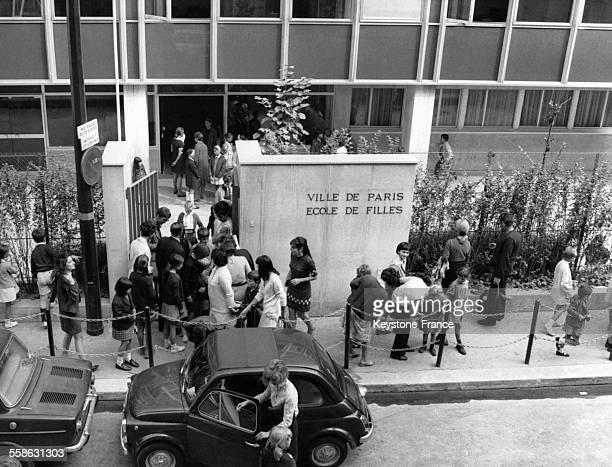 Parents attendant la sortie des classes d'une école des filles le jour de la rentrée scolaire à Paris France le 8 septembre 1969