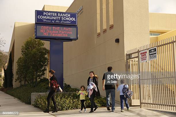 Parents bring their children to Porter Ranch Community School Friday morning while protestors gather at the corner of Tampa and Rinaldi streets on...