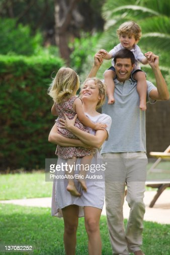 Parents carrying children outdoors : Stock Photo