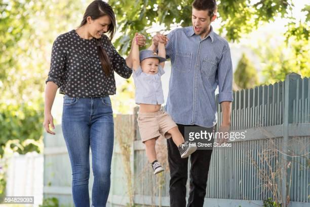Parents carrying son in neighborhood