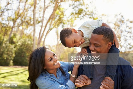 Parents Carrying Son On Shoulders As They Walk In Park : Foto de stock