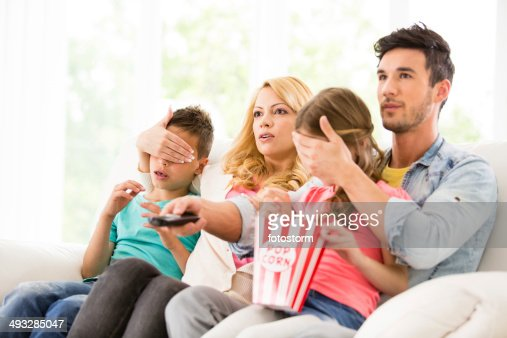 Parents cover their children's eyes while watching TV