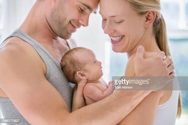 Padres cradling recién nacido bebé