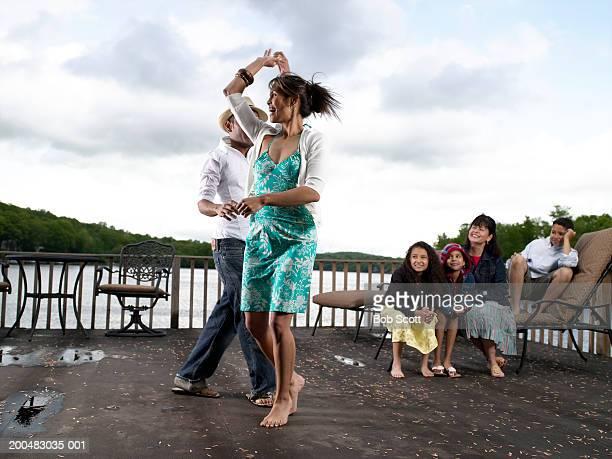 Padres baile, abuela y niños (8 a 12) mira