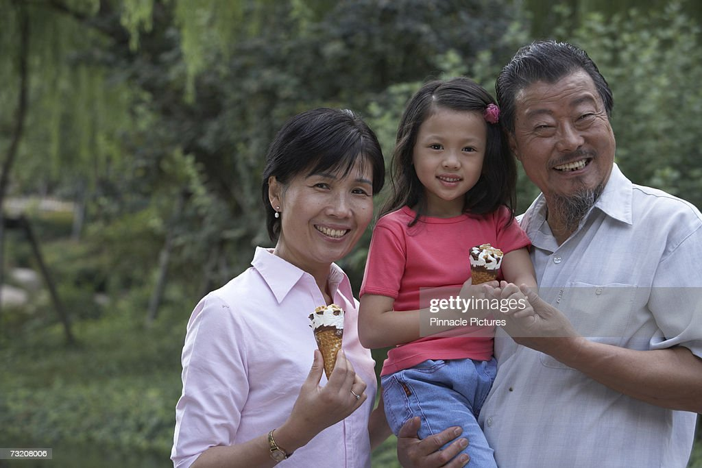 Parents eating ice cream with daughter (4-5) in park, portrait : Stock Photo