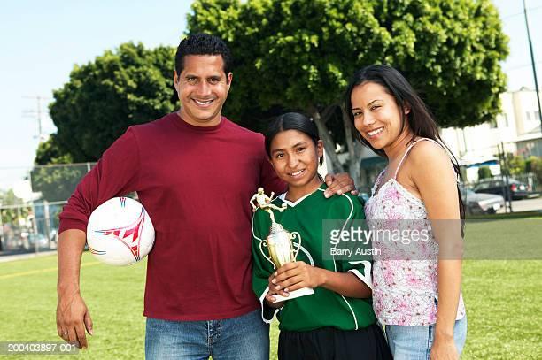 Parents embracing daughter (11-13) holding football trophy, portrait
