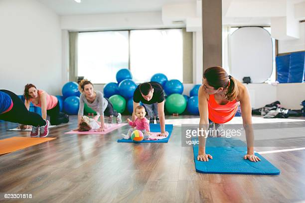 Parents Exercising with Their Babies in a Gym