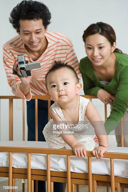 Parents filming baby in crib