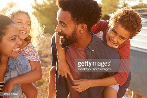 Parents giving their kids piggybacks, waist up, close up : Stock Photo