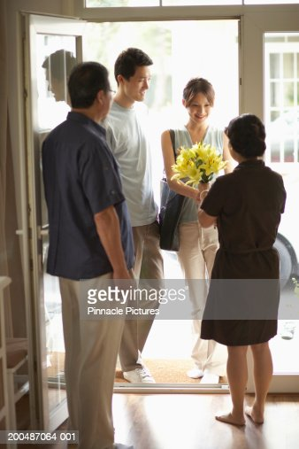 Parents greeting adult offspring at front door : Stock Photo