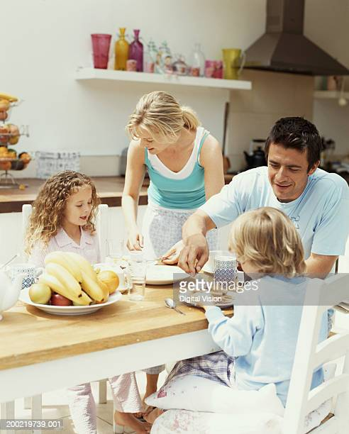 Parents having breakfast with son and daughter (4-6) in kitchen