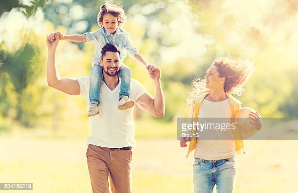 Parents having fun with their little boy outdoors.