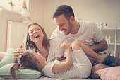 Parents having fun with their little daughter on bed. Family spending time at the morning.