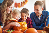 Parents helping children in carving pumpkins