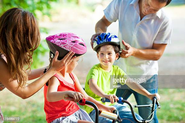Parents Helping Children With Cycling Helmets.