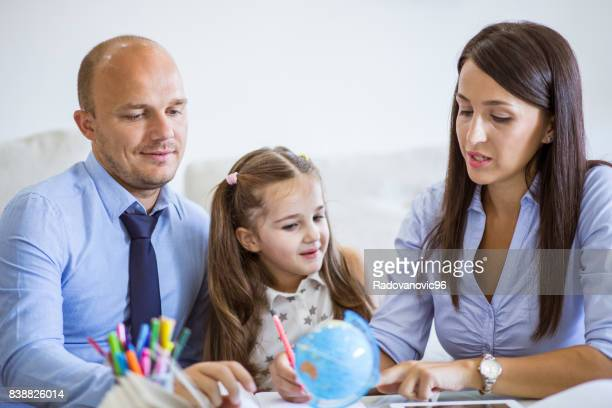Parents Helping Daughter With Homework