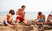 Parents helping son (8-10) build sand castle on beach