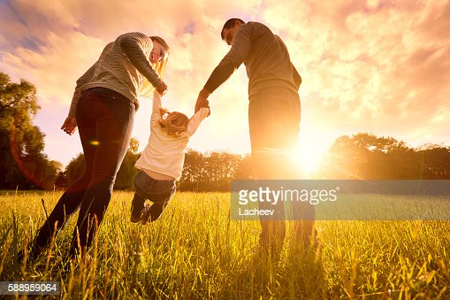 Parents hold baby's hands.  Happy family in park evening : Foto stock