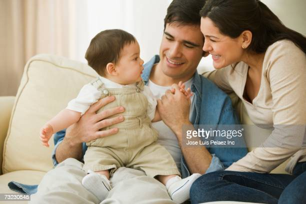 Parents holding baby and smiling on sofa