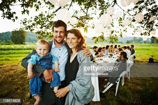 Parents holding baby in front of outdoor table : Stock Photo