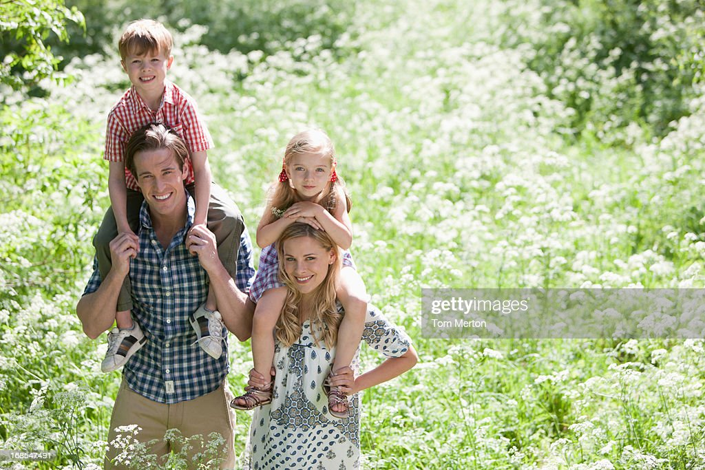 Parents holding children on shoulders in park : Stock Photo