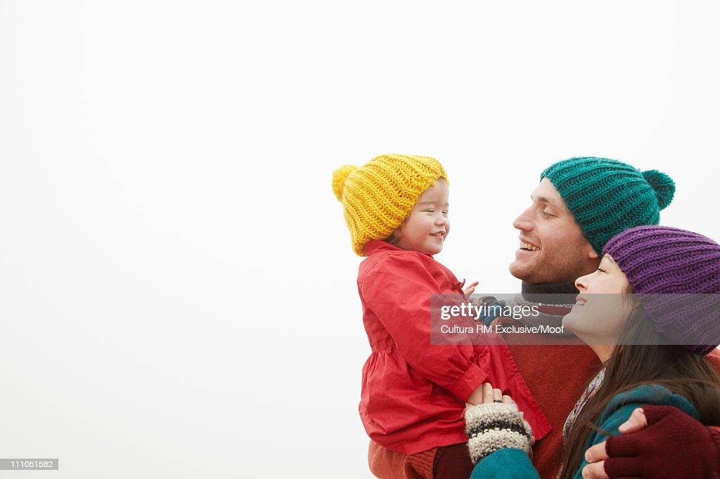 Parents holding daughter outside : Stock Photo