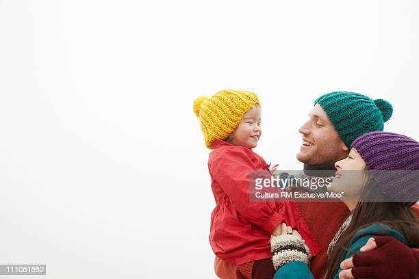Parents holding daughter outside