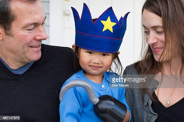 Parents holding daughter with hook and crown