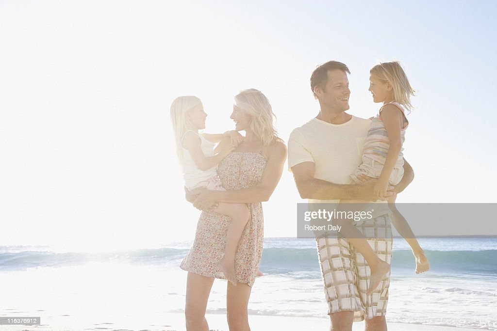 Parents holding daughters on beach : Stock Photo