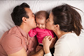 Couple of new parents lying in a bed with her baby girl and kissing her both at the same time