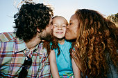 Parents kissing cheeks of daughter outdoors