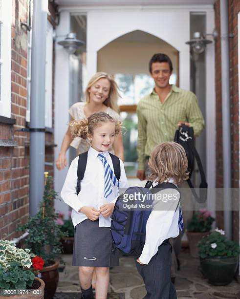 Parents leaving house for school with son and daughter (4-6) smiling