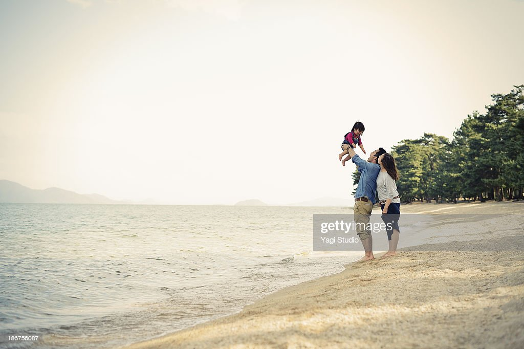 Parents lifting daughter mid air on beach : Stock Photo