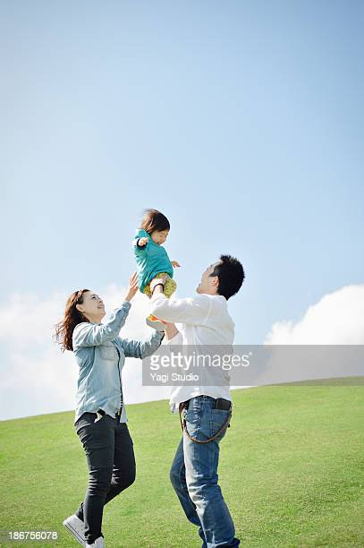 Parents lifting daughter mid air
