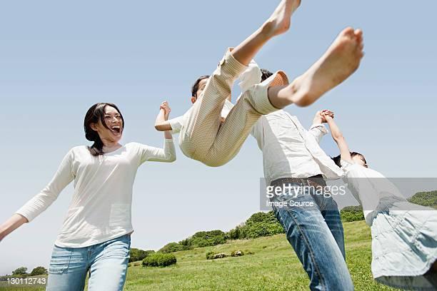 Parents lifting son mid air