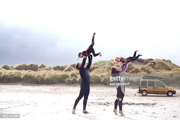 Parents lifting sons on beach