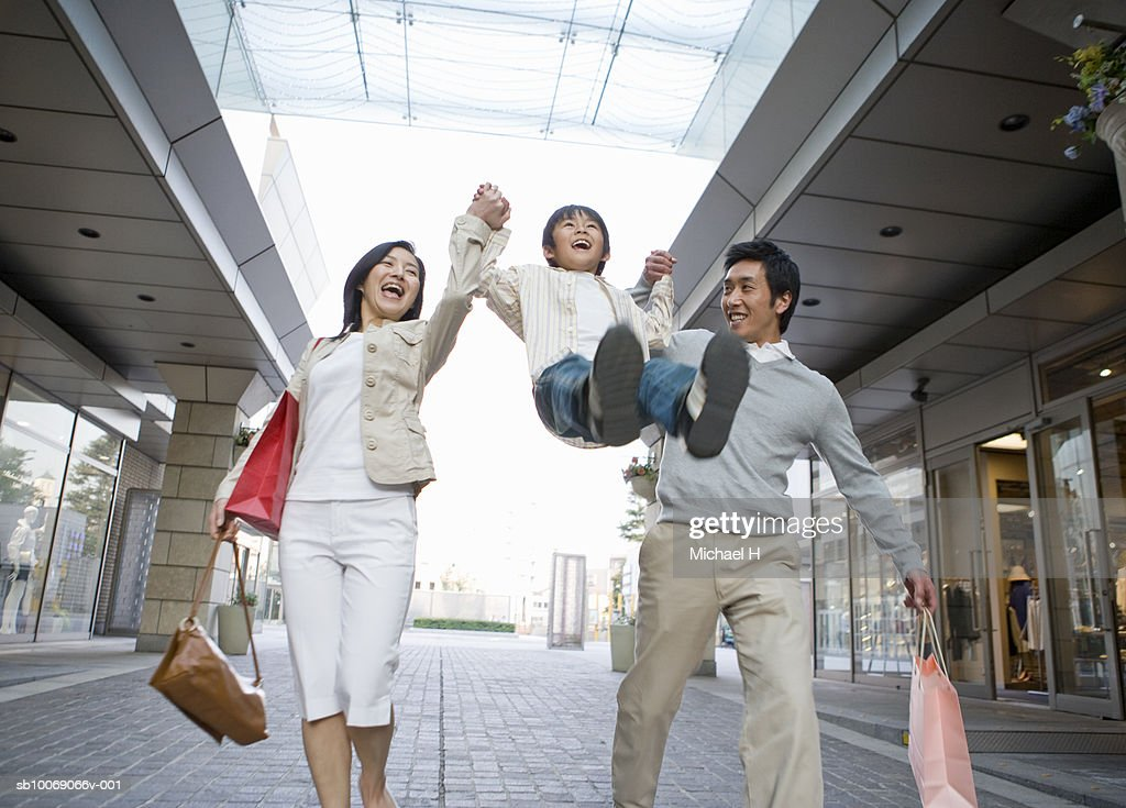 Parents lifting up son (6-7) in shopping mall : Stock Photo
