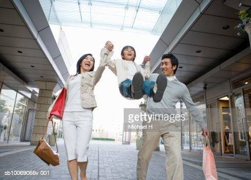 Parents lifting up son (6-7) in shopping mall : Bildbanksbilder