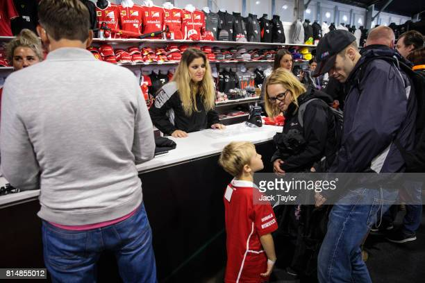 Parents look on as a boy tries on a tshirt at a stall selling branded merchandise during qualifying for the Formula One Grand Prix of Great Britain...