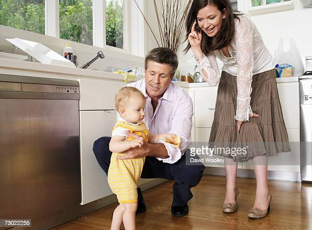 Parents looking at daughter (9-12 months) walking in kitchen