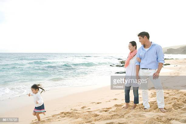 Parents looking at running daughter on beach