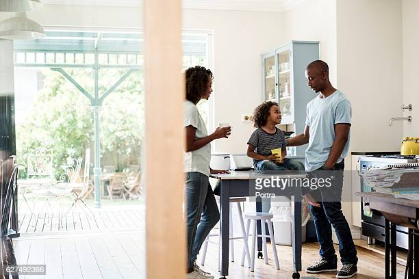 Parents looking at son holding milk glass at home