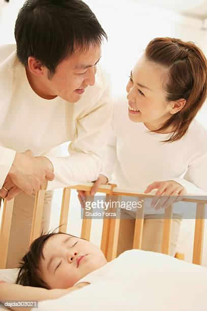 Parents looking at their baby over the baby bed