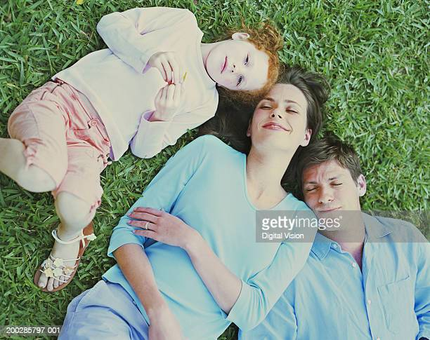 Parents lying on grass with daughter (6-8), overhead view
