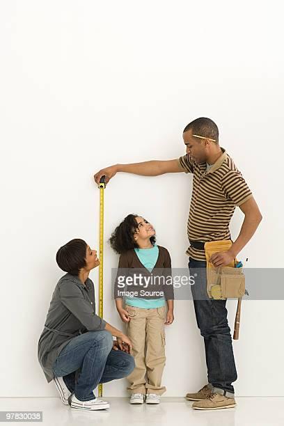 Parents measuring daughter