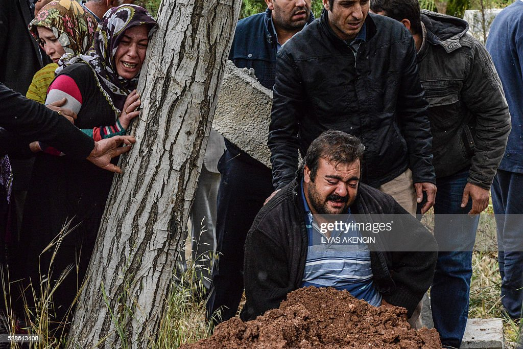 Parents mourn next to a grave on May 6, 2016 in Kilis, during the funeral ceremony of their 5 years old daughter Nisa Done Sezer who was killed the day before after a rocket hit the house. One person was killed and seven more wounded when rockets fired from Syria slammed into the Turkish border region of Kilis, which has been regularly targeted by jihadists this year, the Dogan news agency said. / AFP / ILYAS