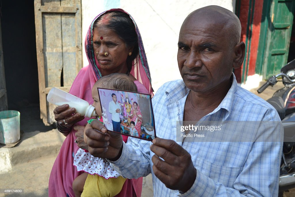 Parents of a women victim named Jankibai aged 26 who died in mass sterilization hold photograph of their daughter outside their home at Chichirda...
