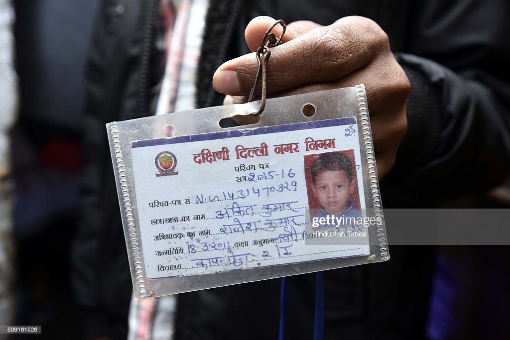 Parents of five-year-old boy Ankit Kumar showing his school Id card on February 9, 2016 in New Delhi, India. Ankit, died at the local MCD school on January 27 drowned in a septic tank, much like Ryan International student Divyansh three days later.